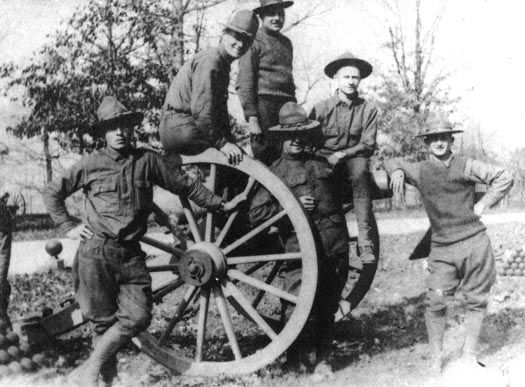 WWI Soldiers from Camp Colt pose on a battlefield gun.